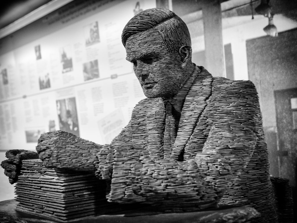 Alan Turing Sorting papers at his desk - LGBT Lawyers