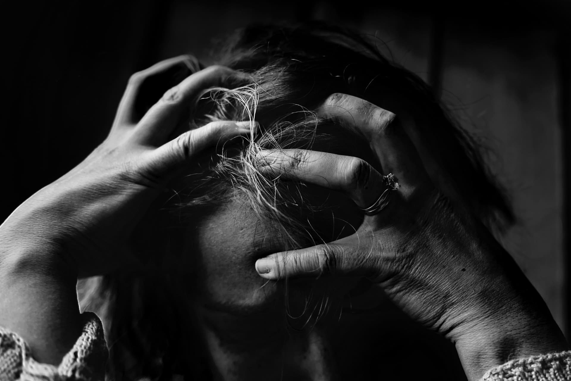 a woman grabs her head because she has lost mental capacity